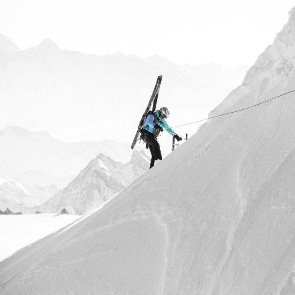 Alpiniste en train de monter le flanc d'une montagne
