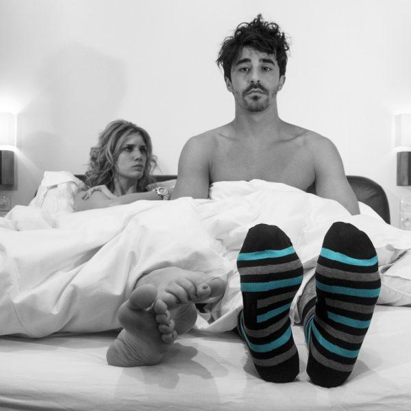couple sous la couette avec les chaussettes de l'homme qui ressorte