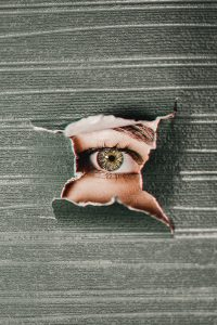 Photographie d'un visage à travers un papier déchiré