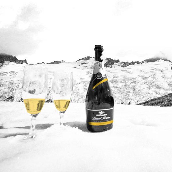 coupes de champagnes et bouteille dans la neige