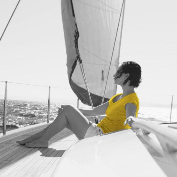 femme assise sur un voilier, cheveux aux vents
