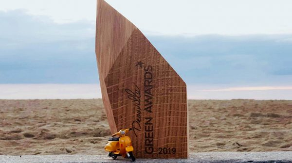 La mobylette jaune avec le deauville green awards sur une plage