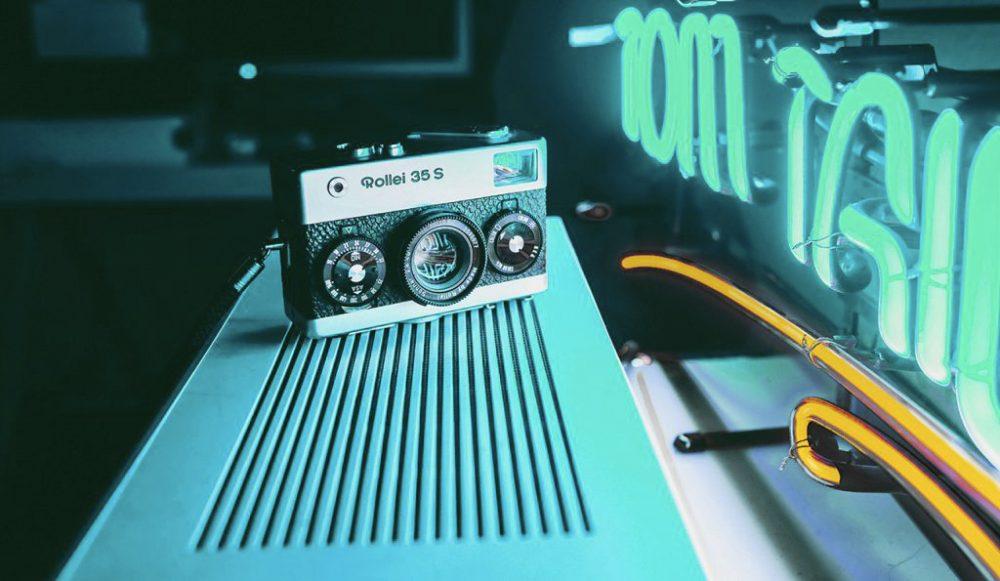 appareil photo vintage devant néons bleus et jaunes