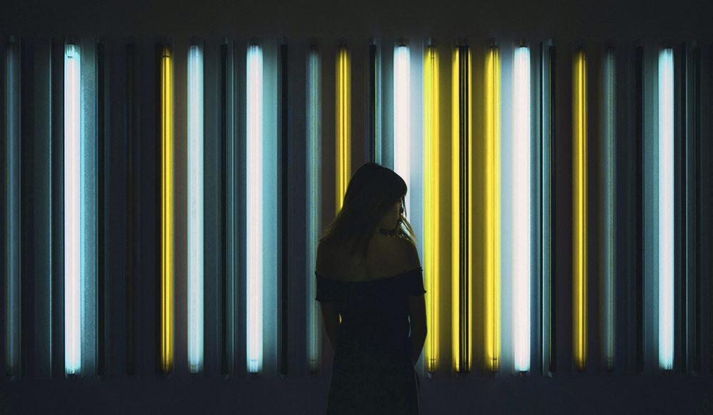 femme devant néons lumineux jaune et bleu