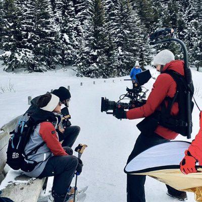 cameraman filmant deux personnes sur un banc dans la neige
