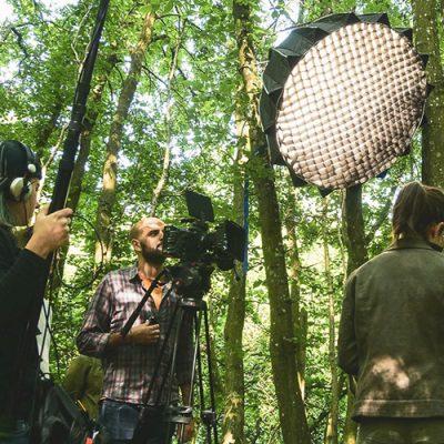 tournage vidéo dans une forêt avec installation lumineuse et cameraman