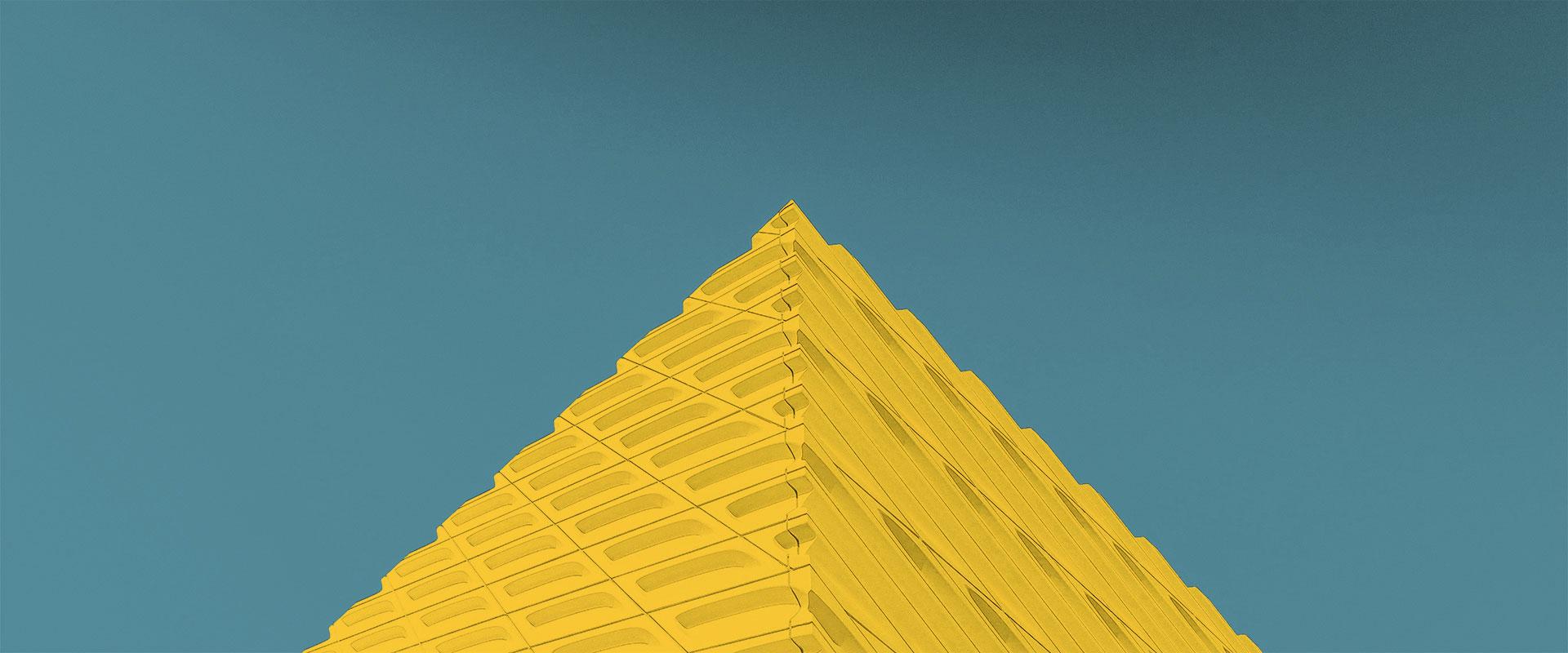 bâtiment architecturale jaune s'imposant dans un ciel bleu