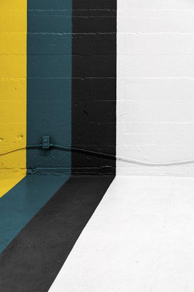 coin d'un mur peint en différentes bandes de couleurs