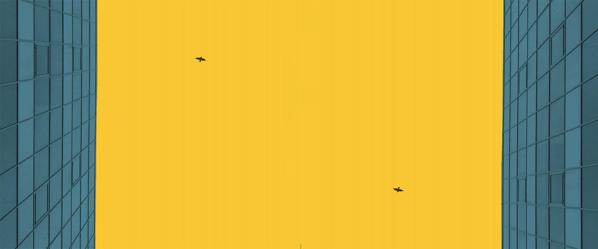bâtiment architecturale bleu avec un ciel jaune et des oiseaux