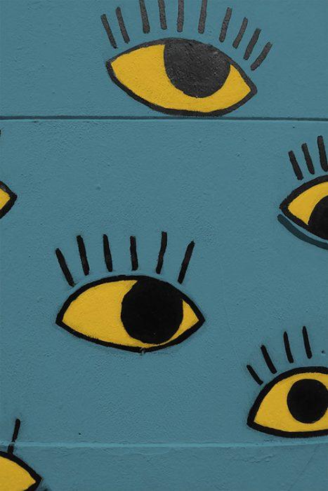 mur street art avec yeux jaune sur mur bleu